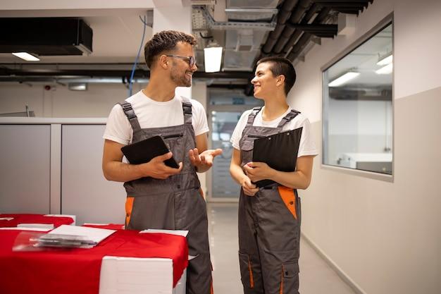Robotnicy przemysłowi rozmawiają o nowej pracy na korytarzach fabrycznych.