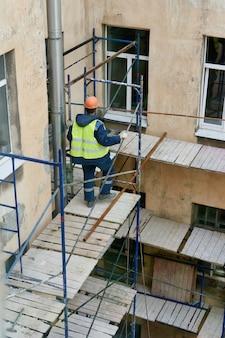 Robotnicy wznoszą rusztowania do naprawy elewacji budynku