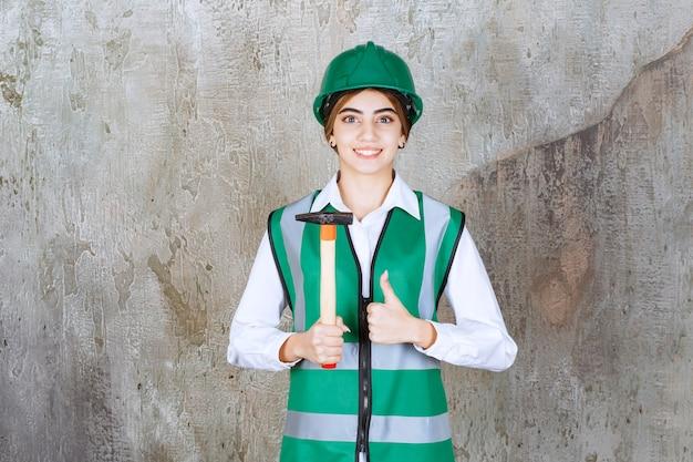 Robotnik budowlany w zielonym kasku trzymający młotek i dający kciuk w górę