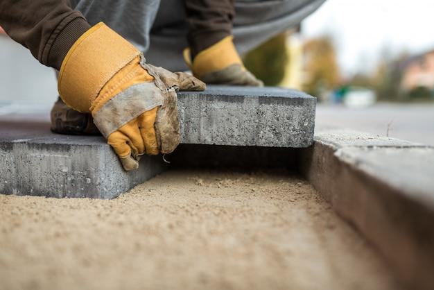 Robotnik kłaść zewnętrzne brukowe kamienie