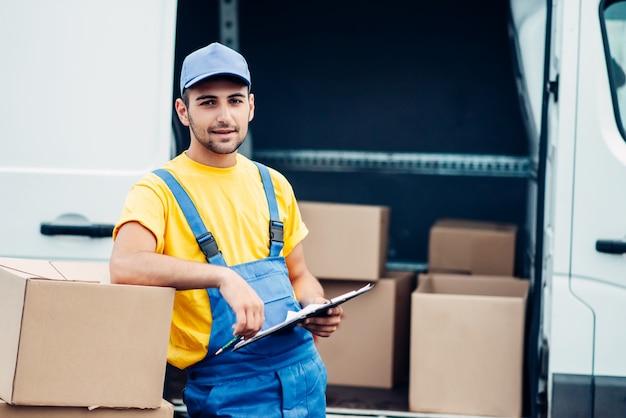Robotnik lub kurier trzyma w rękach karton