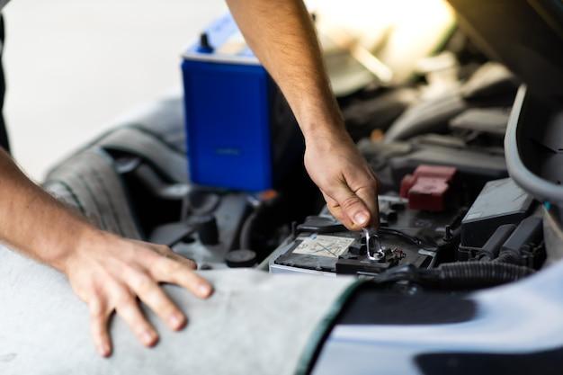 Robotnik mechanik samochodowy sprawdzanie i wymiana akumulatora samochodowego. konserwacji samochodów i koncepcji garażu auto serwis.