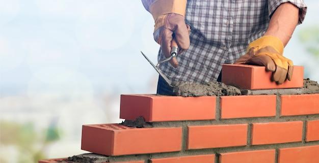 Robotnik murarski instalujący mur ceglany