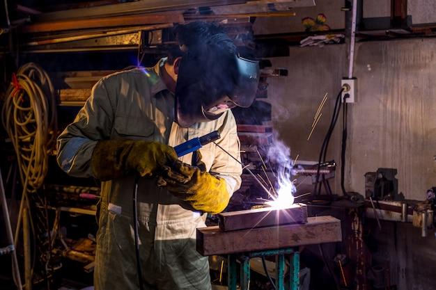 Robotnik robotnik w fabryce spawania konstrukcji stalowej z maską ochronną i mundurem.