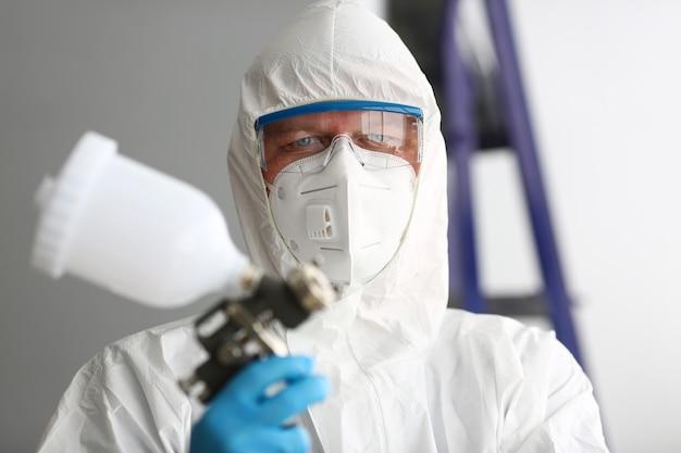 Robotnik trzymać w ramieniu pistoletu airbrush na sobie strój ochronny