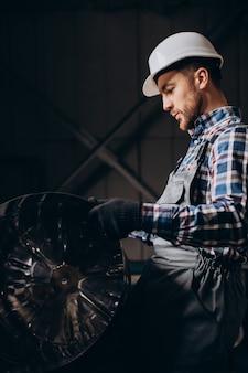 Robotnik w kasku pracujący z konstrukcjami metalowymi w fabryce