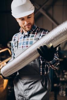 Robotnik w kasku pracującym z metalową rurką w fabryce