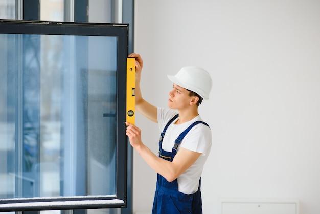 Robotnik w kombinezonie montujący lub regulujący plastikowe okna w salonie w domu