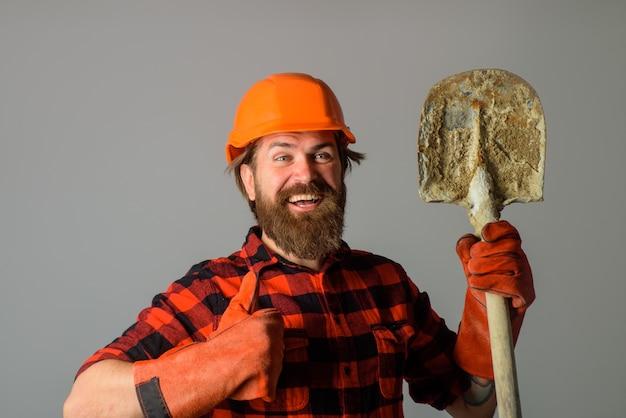 Robotnik z łopatą pokazuje kciuk w górę budowniczy w rękawicach roboczych trzyma technologię budownictwa łopatowego