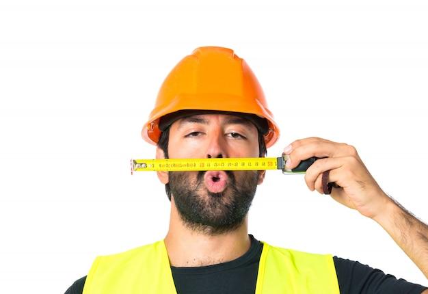 Robotnik z miernikiem jak wąsy na białym tle