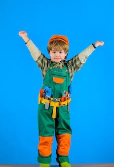 Robotnik z narzędziami naprawia mały chłopiec w mundurze konstruktora z paskiem narzędziowym mały dzieciak mechanik budowniczy