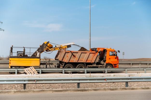 Roboty drogowe. okruchy asfaltu z recyklingu są wylewane przez przenośnik taśmowy do nadwozia ciężarówki