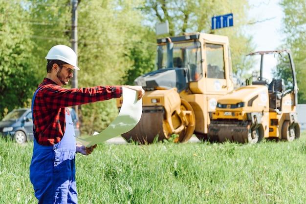 Roboty drogowe w pobliżu maszyny do układania asfaltu. naprawa dróg. pracownik służby drogowej w pobliżu lodowiska.