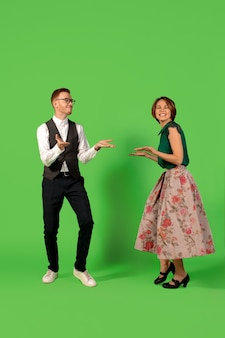Rock n roll. old school fashioned młoda kobieta taniec na białym tle na tle zielonym studio. młody elegancki mężczyzna i kobieta.