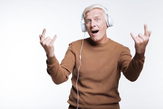 Rock nigdy nie umiera. podekscytowany starszy mężczyzna słucha muzyki w słuchawkach i obiema rękami pokazuje znak rogów