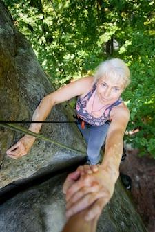 Rockclimber pomaga kobiecie wspiąć się na szczyt góry