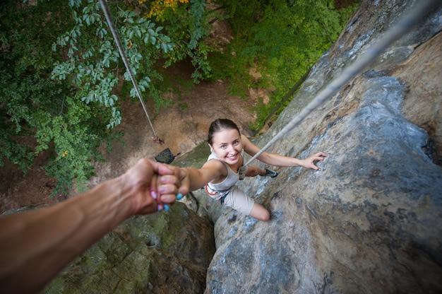 Rockclimber pomaga kobiecie wspinać się na szczyt góry