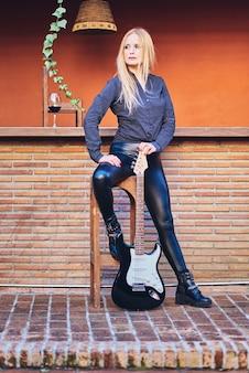 Rocker kobieta pozuje z gitarą.