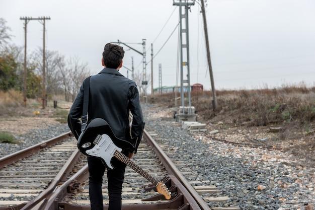 Rocker w okularach przeciwsłonecznych spacerujący z gitarą elektryczną po opuszczonych torach kolejowych.