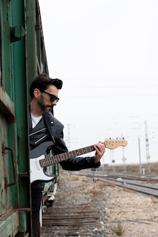 Rocker z okularami przeciwsłonecznymi i gitarą elektryczną wsiadł do opuszczonego wagonu