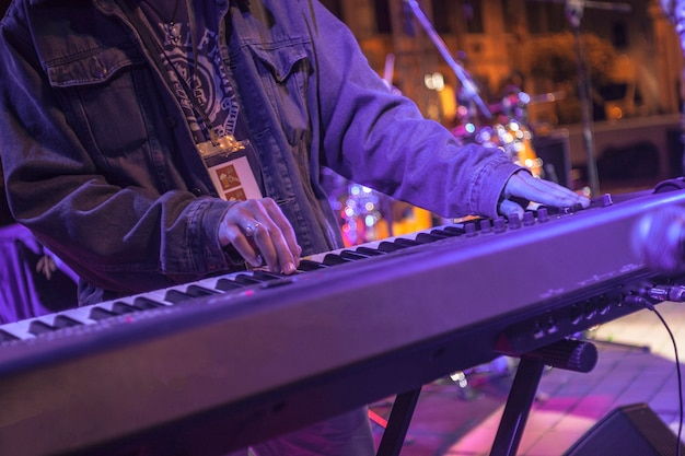 Rockowy klawiszowiec gra na żywo pod światłami kolorowych reflektorów