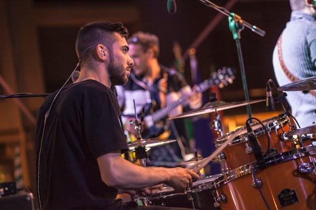 Rockowy perkusista gra w nocy podczas koncertu.
