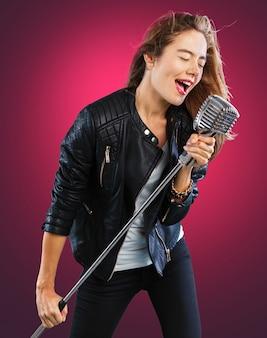 Rockstar kobieta śpiewa z mikrofonem w stylu retro vintage