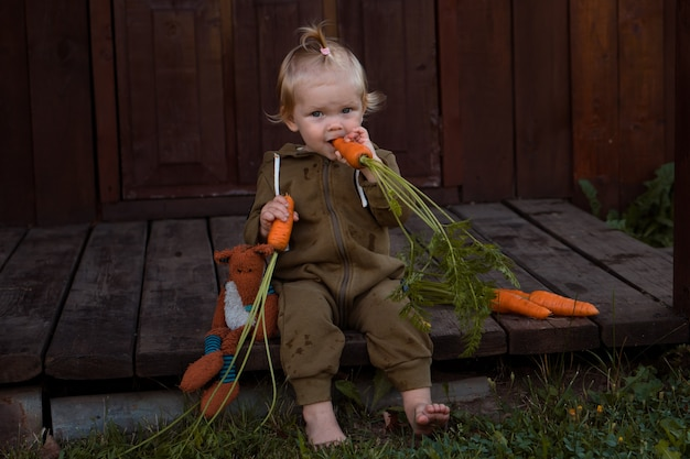 Roczna blond dziewczynka boso je świeżą marchewkę i bawi się zabawką na podwórku lub w ogrodzie