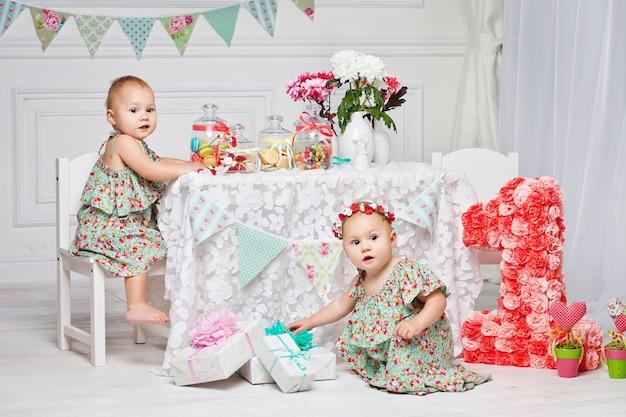 Roczne bliźniaki w dniu urodzin. śliczne bliźniaczki świętują swoje pierwsze urodziny