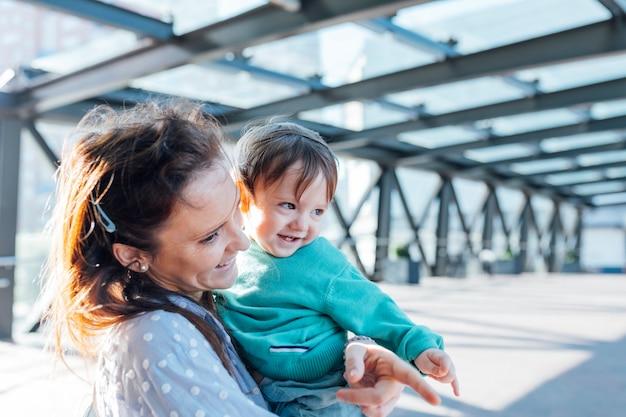 Roczne dziecko o figlarnym spojrzeniu uśmiechnięte przyłapane przez swoją tysiącletnią matkę na ulicy