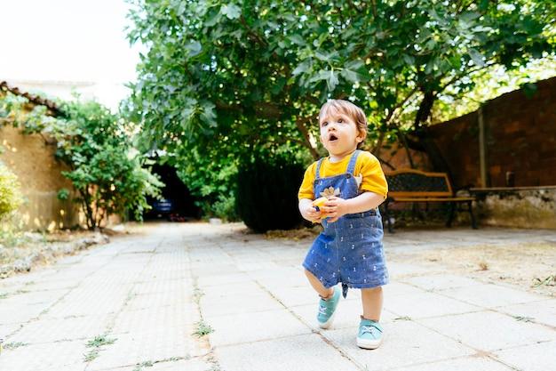 Roczne dziecko z zaskoczeniem stawia pierwsze kroki na podwórku