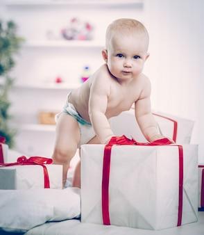 Roczne słodkie dziecko bawi się zakupami w pudełkach na sofie w pokoju dziecinnym