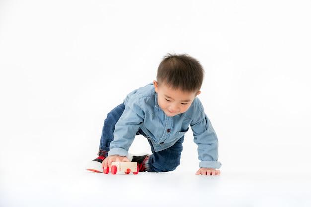 Roczniak azjatykci chłopiec szczęśliwy bawić się drewnianego samochód, pracowniany krótkopęd.