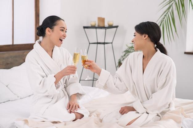 Rocznica spotkania. zadowolona szczęśliwa para pije szampana podczas obchodów rocznicy spotkania
