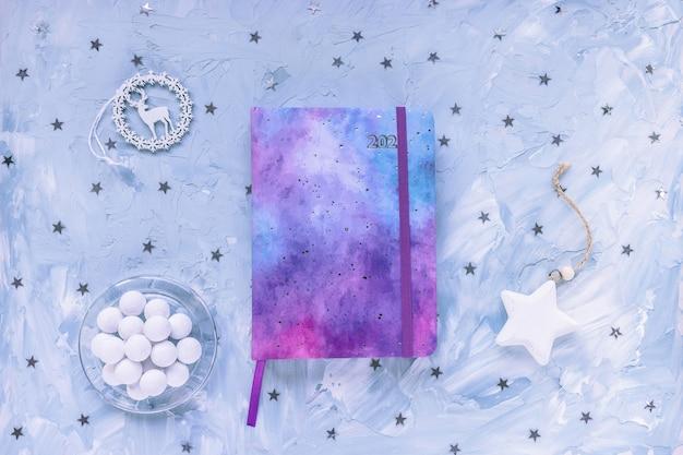 Rocznik 2021, dekoracja czekolady i gwiazdek na biurku, niebieskie tło.