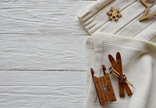Rocznik bożenarodzeniowe dekoracje na białym drewnianym tle. biała wełniana czapka i szalik, drewniane narty, sanie, płatek śniegu i gwiazda. widok z góry. zimowe tło.