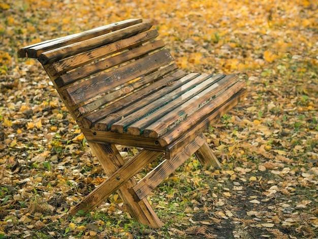 Rocznik drewniana ławka w jesień parku.