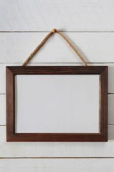Rocznik drewniana rama puste wieszać na drewnianej ścianie.