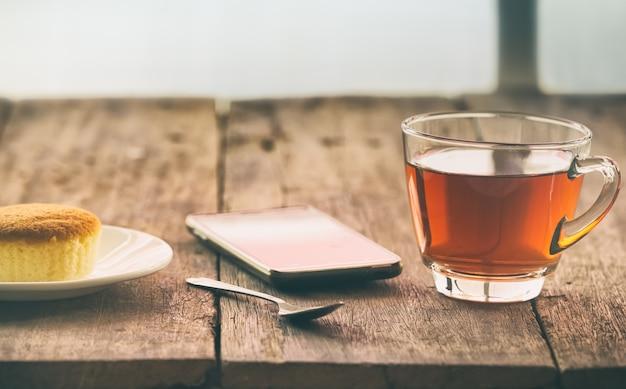Rocznik filiżanka herbata na drewnianym stole w ranku tle.