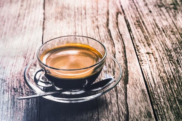 Rocznik filiżanka kawy na nieociosanym drewno stole który stosownym dla tła i wszystkie grafiki de