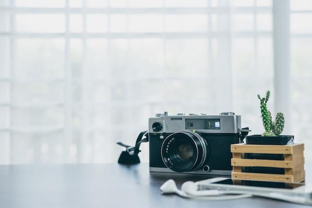 Rocznik kaktus umieszczający na drewnianym stole z białym tłem i kamera