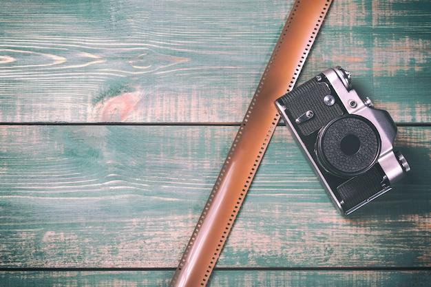 Rocznik kamera z filmem na zielonym drewnianym tle.
