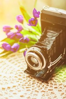 Rocznik kamera z pięknym bukietem kwiaty na trykotowym obrusie. stary rocznik wciąż życia pojęcie.