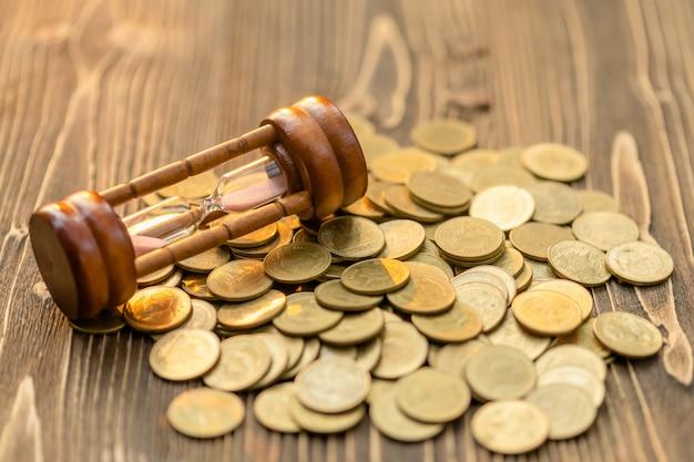 Rocznik klepsydra, sandglass lub moneta na drewnianym stole. pojęcie oszczędności czasu i pieniędzy
