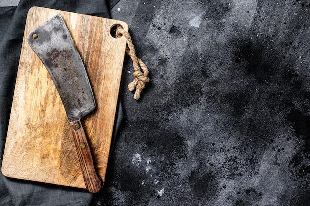 Rocznik rzeźnika mięsny tasak na betonowej desce. czarna powierzchnia. widok z góry. skopiuj miejsce