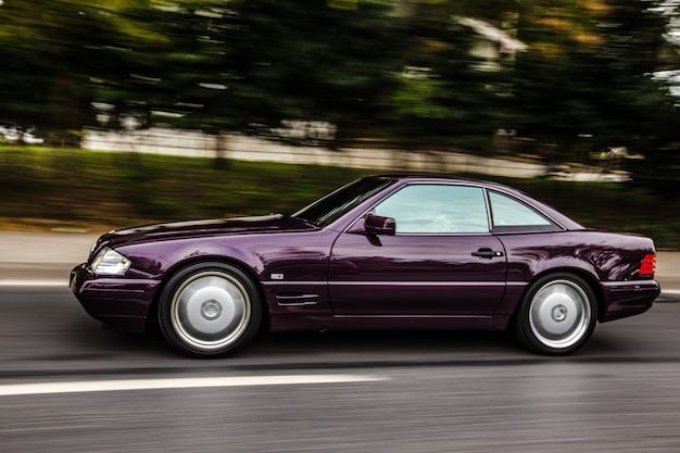 Rocznika bordowego sedanu samochodowy jeżdżenie na drodze, boczny widok.
