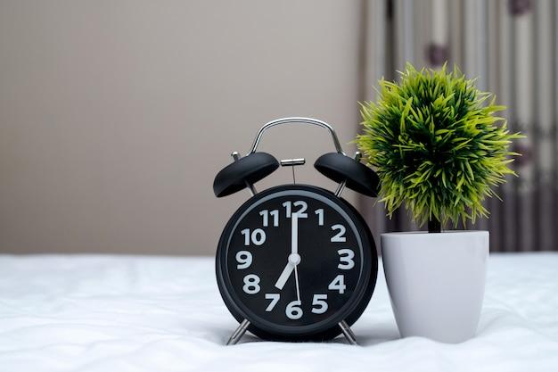 Rocznika budzik i mały drzewo na łóżku