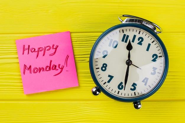 Rocznika budzik i szczęśliwego poniedziałku życzenie. widok z góry leżący na płasz- czu. żółte drewniane tło.