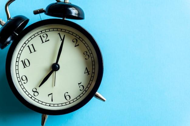 Rocznika budzik na błękitnym czystym copyspace. zarządzanie czasem i koncepcja czasu.