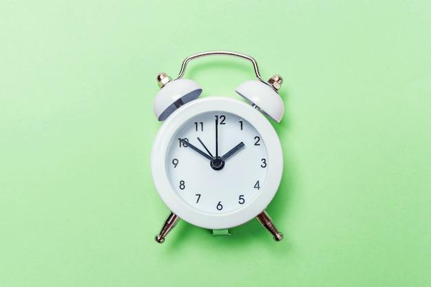 Rocznika budzik odizolowywający na zielonym pastelowym tle